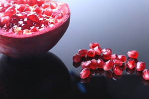 Pomegranate seeds and Beautiful ripe pomegranate on black mirror background with place for copy space.