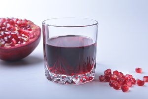 Glass with pomegranate juice Pomegranate seeds and Beautiful ripe pomegranate on white background with place for copy space.