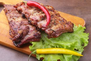 grilled barbecued ribs with lettuce leaves, hot chili pepper and sauce on wooden cutting board.