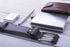 Gadgets and accessories for men on light wooden background. Fashionable men s belt, wallet, lighter, Stainless hip flask and pen.