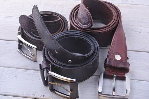 Fashionable men's leather belt. Gadgets and accessories for men on light wooden background.