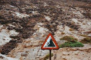 Warning road sign, beware of falling rocks