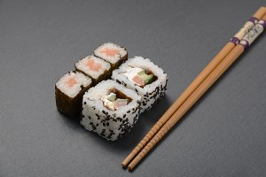 sushi on the black table with chopsticks