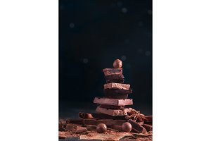 Stack of broken chocolate pieces on a dark background with copy space. Confectionery food photography in low key.