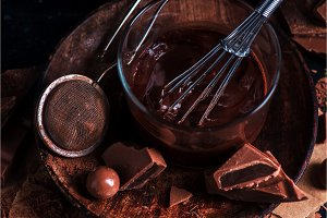 Close-up of chocolate glazing in a glass cup with a whisk. Cocoa powder, cinnamon and other spices on a black background. Macro food photography with copy space.