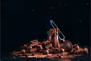Header with cinnamon in a glass jar, scattered cocoa powder and pieces of broken chocolate on a dark background with copy space. Dessert ingredients in low key.