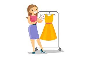 Caucasian woman cutting price tag off new dress.