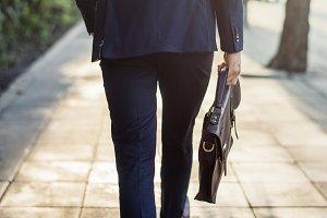 Walking business man holding his bag
