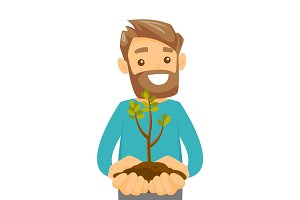 Caucasian white man holding green plant in soil.