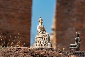 Buddha figurine with temple ruins on the background