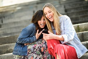 Two smiling girls looking smartphone