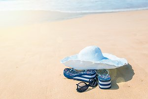 hat, sun glasses and flip flops over