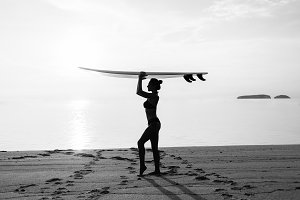 woman with surfboard on the beach