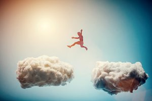 Man jumping from one cloud to anothe