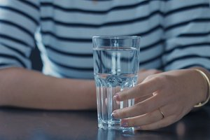 closeup of woman's hand with glass of water