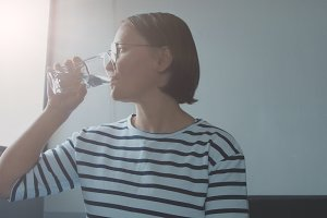 woman in top with stripes drinking water