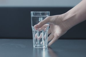 woman's hand picking a glass of water