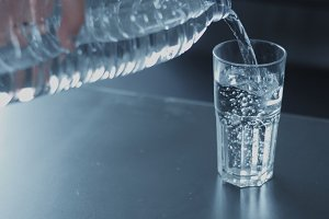 closeup slowmotion of glass fulling with water from bottle