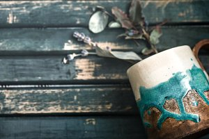cup with flowers on a wooden background