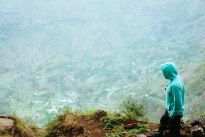 Traveler on the mountain edge overlooking the rural landscape of Paul valley. Santo Antao Island, Cape Verde
