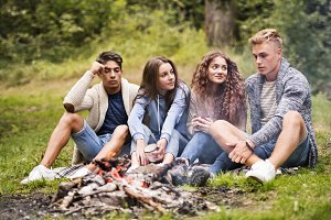 Teenagers camping in nature, sitting at bonfire.