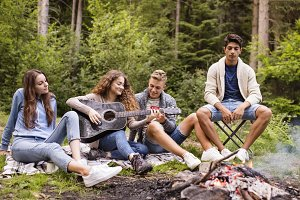 Teenagers wit a guitar camping in forest.