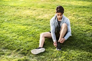 Runner in the city sitting on grass tying shoelaces.