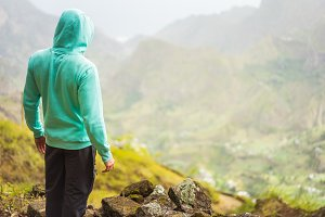 Tourist in hoodie in front of rural landscape with mountains, on the way of the Paul Valley. Santo Antao Island, Cape Verde