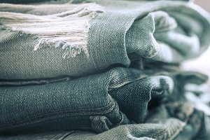 A stack of jeans on a wooden background