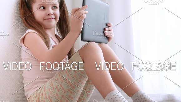 Baby Little Girl Holding And Using Pc Tablet And Sits On The Floor In Room