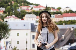 Beautiful young tourist with camera in the old town.
