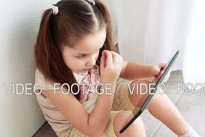 Baby little girl holding and using pc tablet and sits on the floor in room. Child learning to do makeup