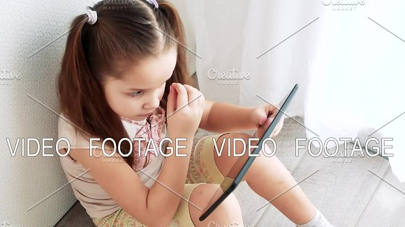 Baby Little Girl Holding And Using Pc Tablet And Sits On The Floor In Room Child Learning To Do Makeup