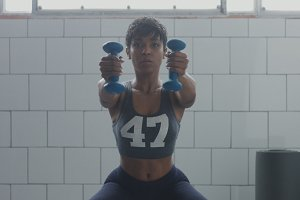 black woman portrait during weight training closeup with foucus on hand with weight