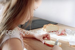 little child making sandwich with butter and sausage