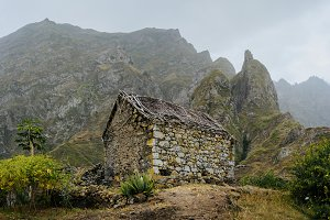 Ruined local storehouse nestled into incredible scenery with steep mountain rocks and vertical peaks. Trekkingtrail on Santo Antao Cape Verde