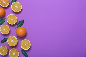 Fresh oranges on the purple background. Copy space