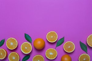 Fresh oranges on the purple background
