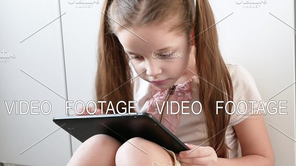 Emotional Girl Is Playing In Video Games Using Tablet Portrait Of Child With Electronic Gadget