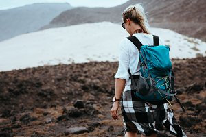 Woman hiker walking on barren rocky terrain among black volcanic boulders and white sand dunes. Sao Vicente Cape Verde