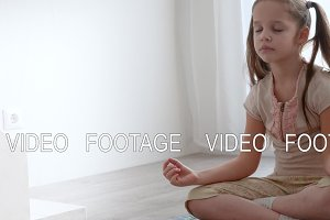 little cute girl sitting in yoga lotus pose and meditates near the window