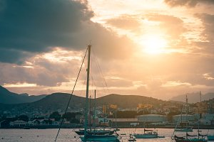 Sail Yacht on anchor in Mindelo Harbor on sunset. Golden flares light the cloudy sky. Sao Vicente Island, Cape Verde