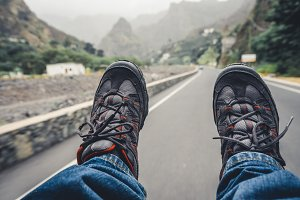 Relaxing feet with trekking footwear hanging from pickup car after long trek way. Santo Antao Island, Cape Verde