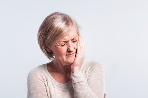 Studio portrait of a senior woman in pain.