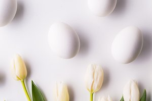 Flowers and white eggs on a white background. Flat lay.