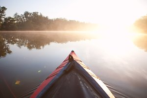Paddling kayak on foggy river