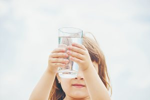 the child holds a glass of water