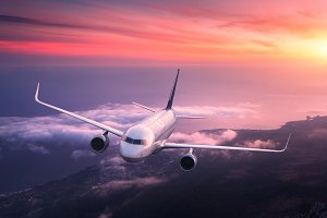 Big airplane is flying in red sky over the clouds