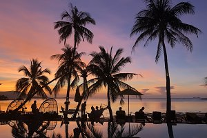 Beautiful tropical beach and swimming pool with palm trees silhouettes.