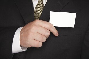 Businessman in Suit Holding Card